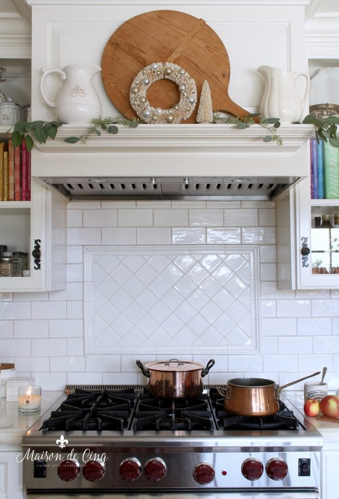 christmas kitchen tour stove range mantel decorated with a wreath, eucalyptus, and white pitchers holiday decor