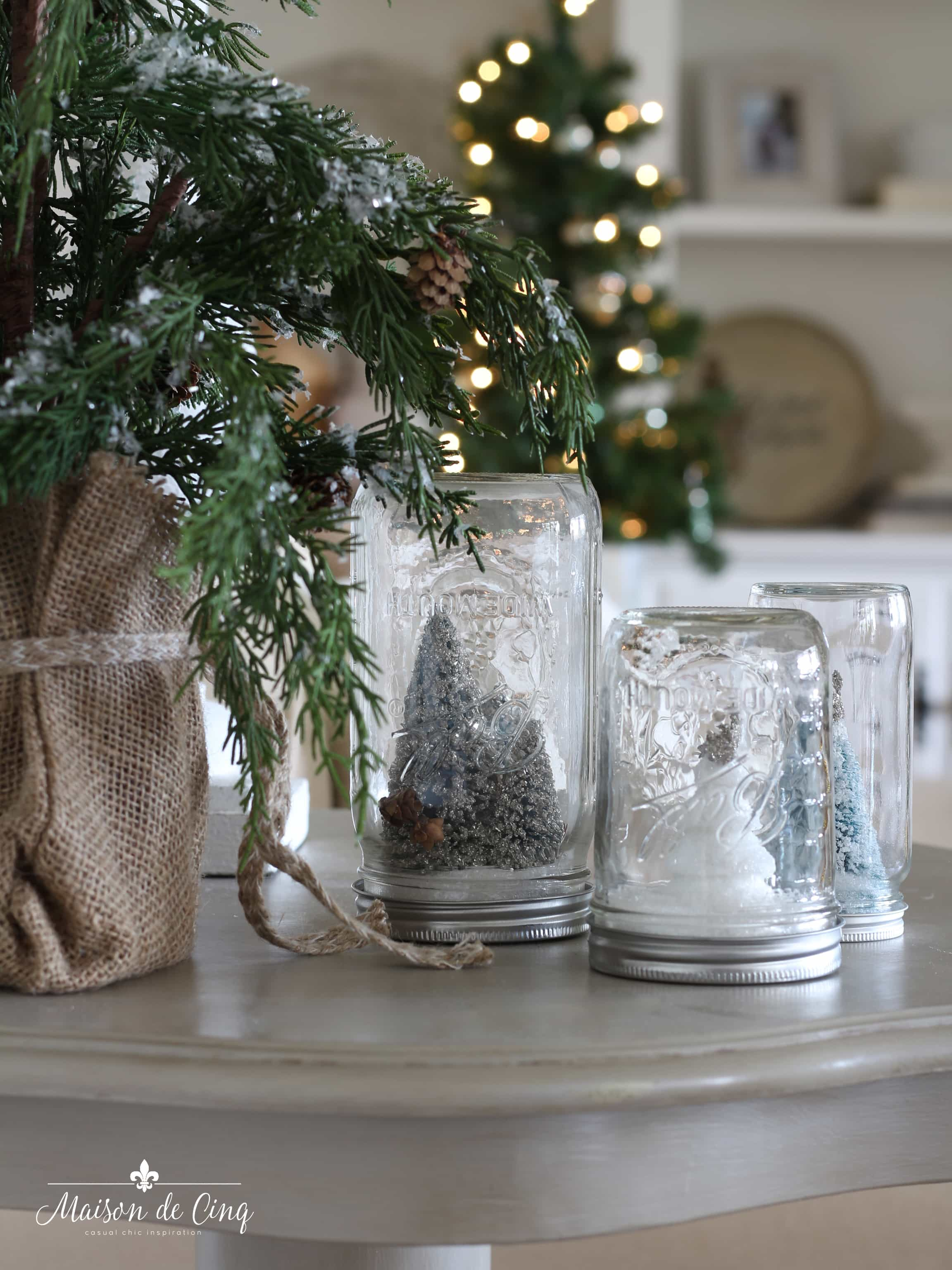 French farmhouse Christmas grouping of mason jar snow globes on table Christmas tree holiday decor