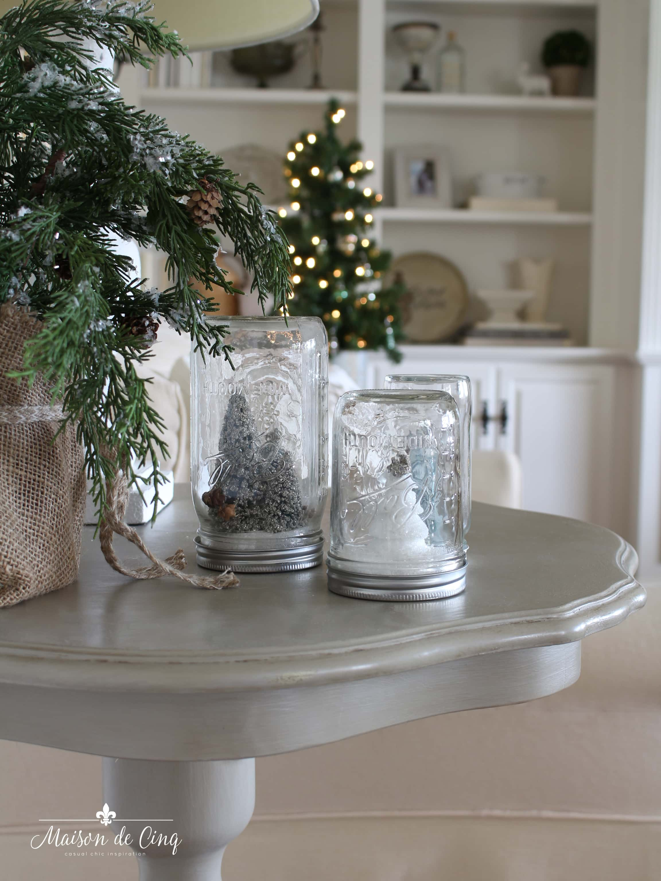 French farmhouse Christmas mason jar snow globes on table with Christmas tree behind gorgeous holiday decorating