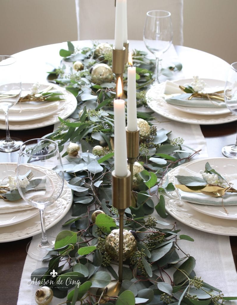 green and white tablescape overview brass candlesticks gold ornaments on runner of eucalyptus with white plates