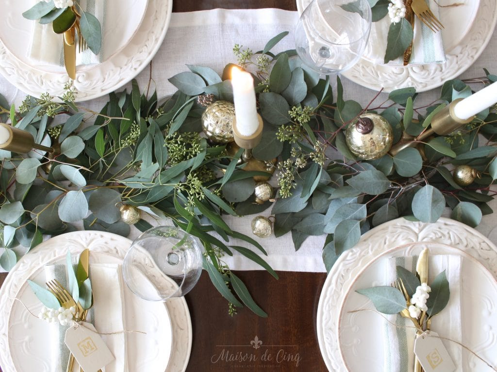 green and white christmas tablescape with eucalyptus candles and white plates gorgeous