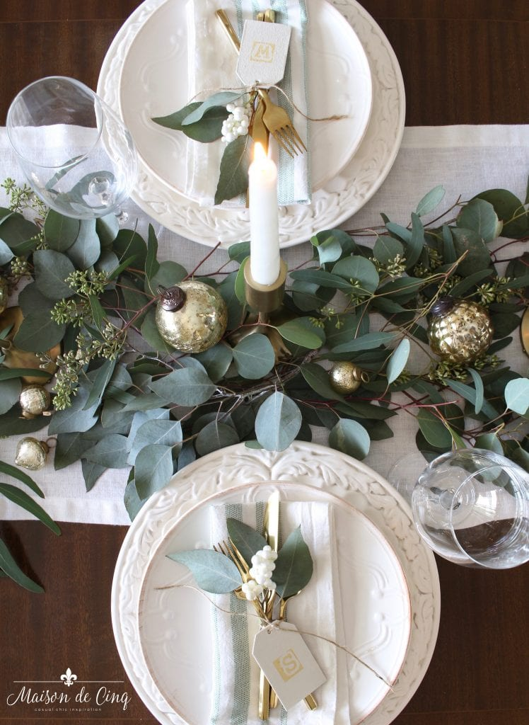 green and white christmas tablescape overhead view white plates runner eucalyptus with gold candlesticks and ornaments gorgeous holiday table decor