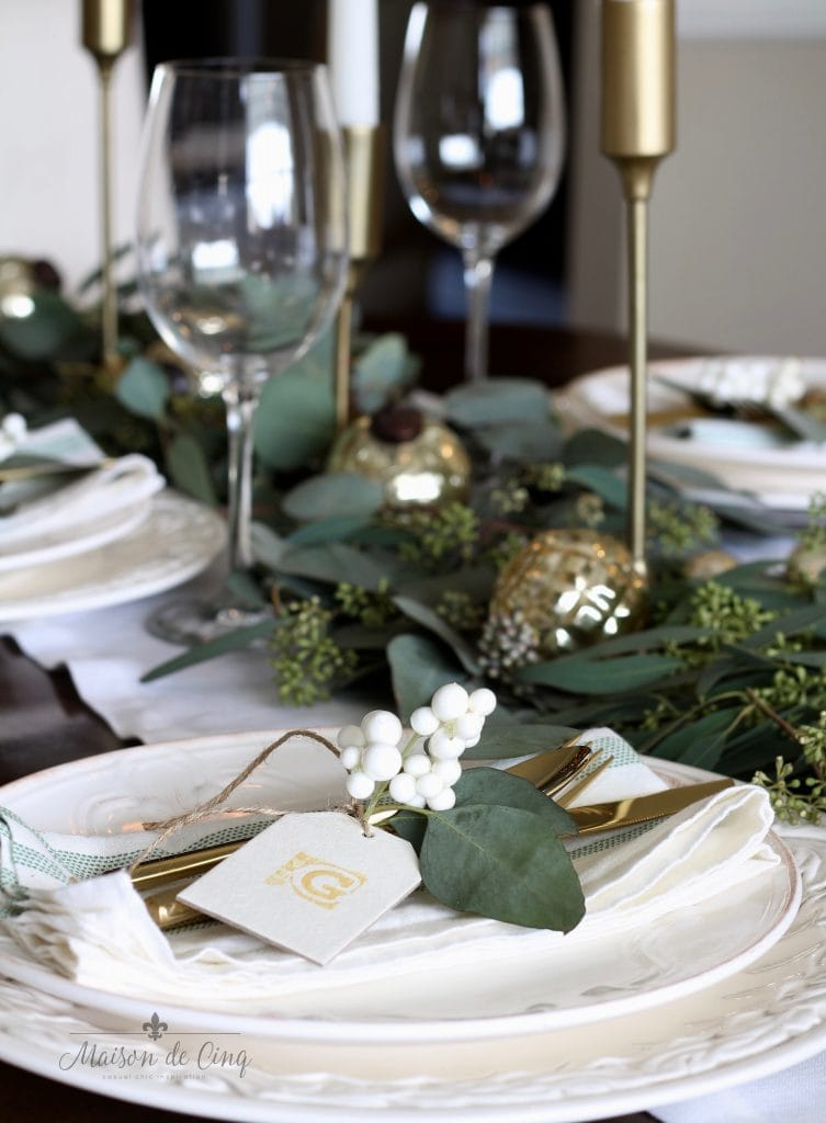 green and white christmas tablescape wine glasses brass candlesticks gold ornaments white dinnerware
