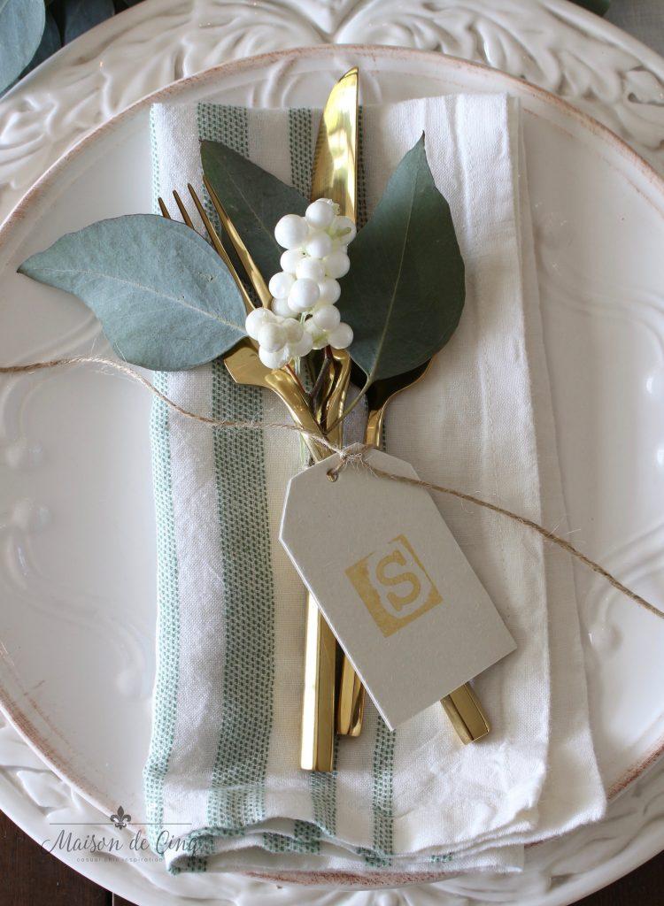green and white christmas tablescape with white plates and charger gold flatware hand stamped place card white berries