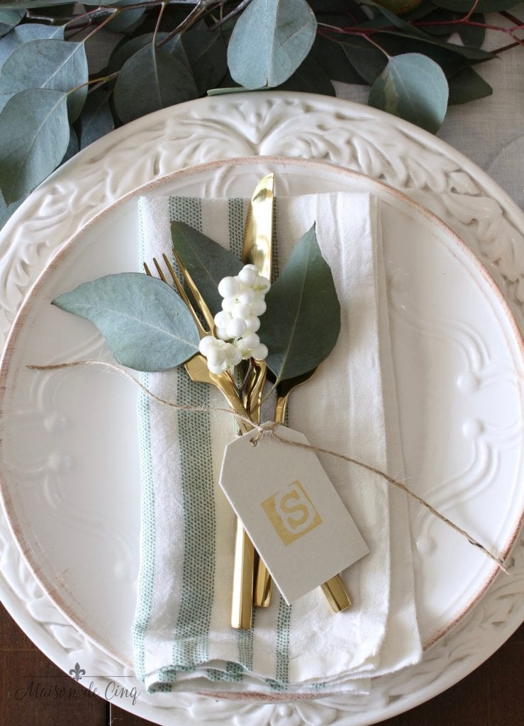 green and white tablescape white plates with striped napkins eucalyptus gold flatware
