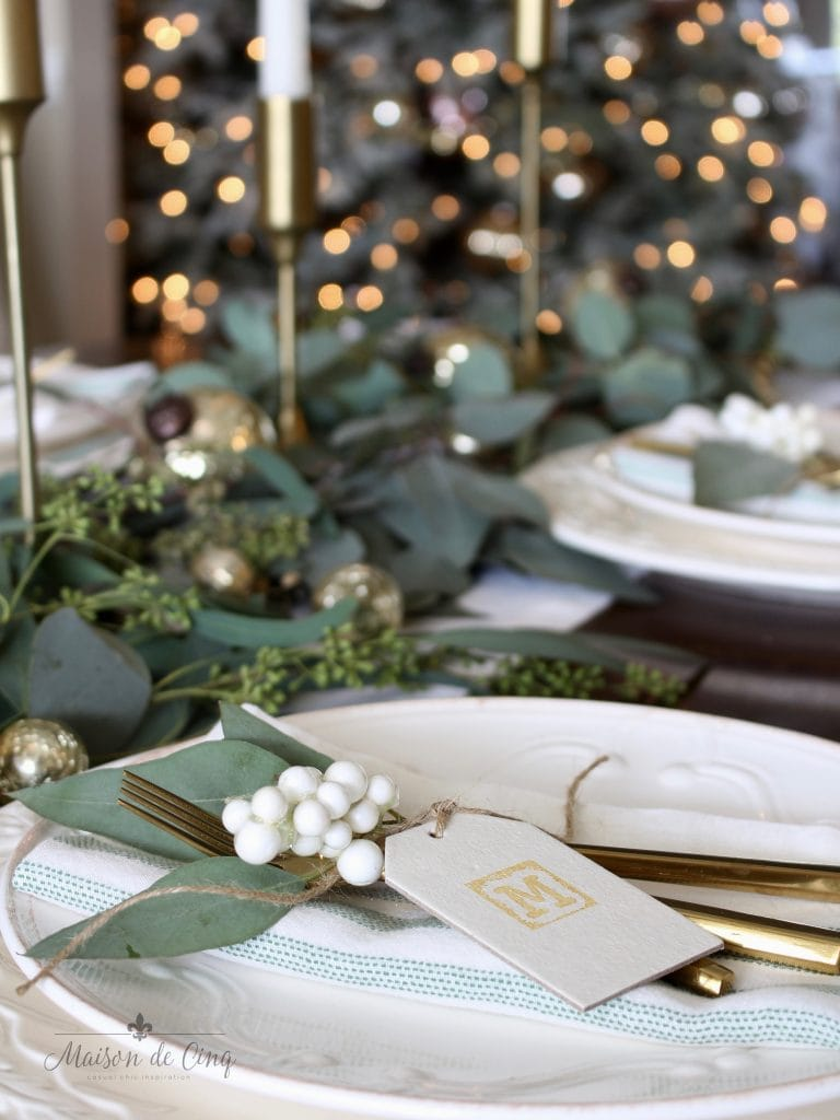 green and white tablescape with christmas tree lights in background white plates gold flatware