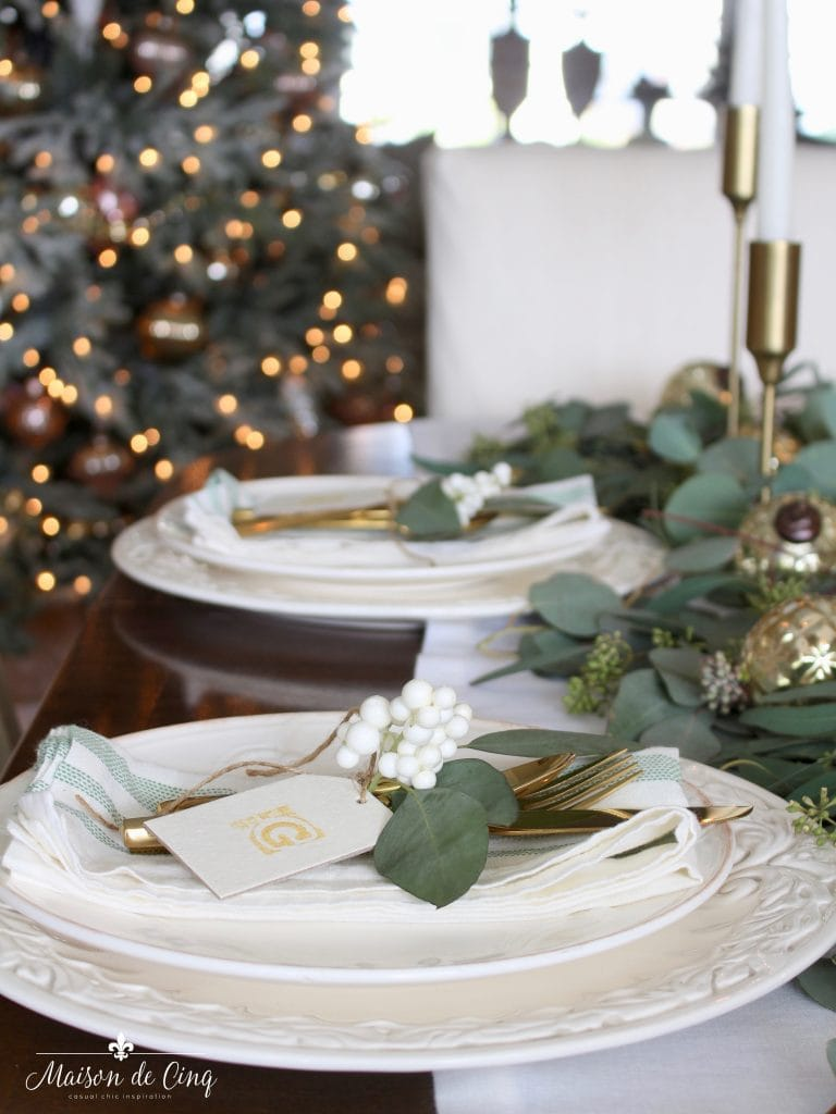 green and white christmas table looking at christmas tree white plates greens brass candle holders gorgeous holiday table