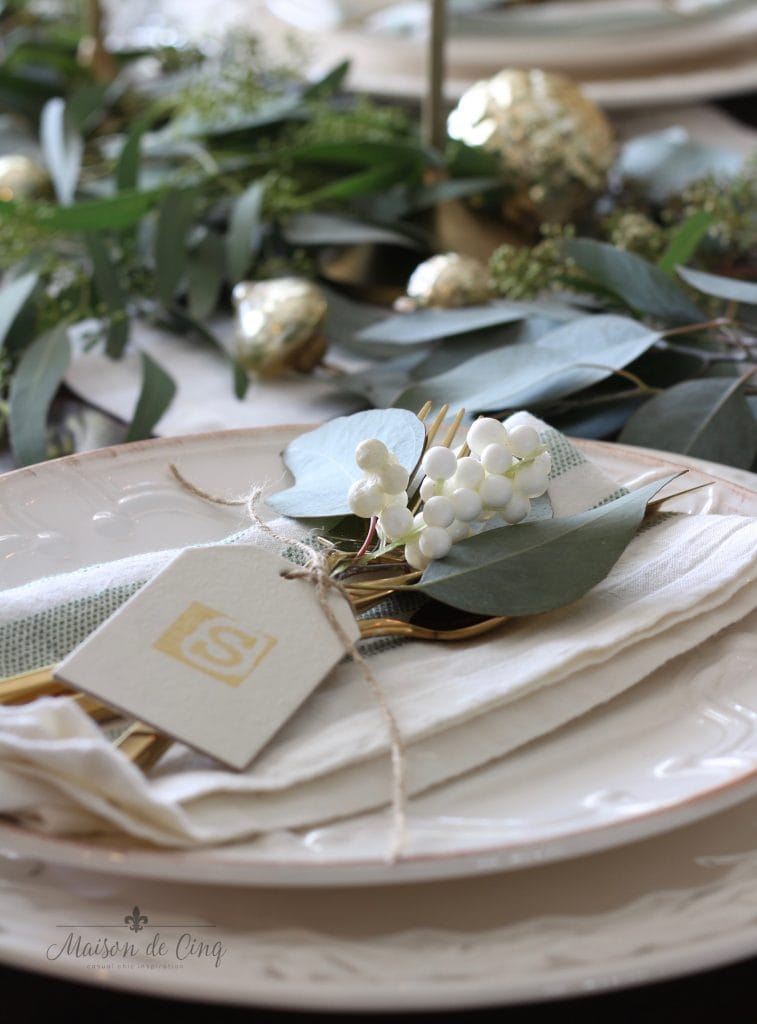 green and white christmas tablescape white plates hand stamped place cards with white berries and eucalyptus