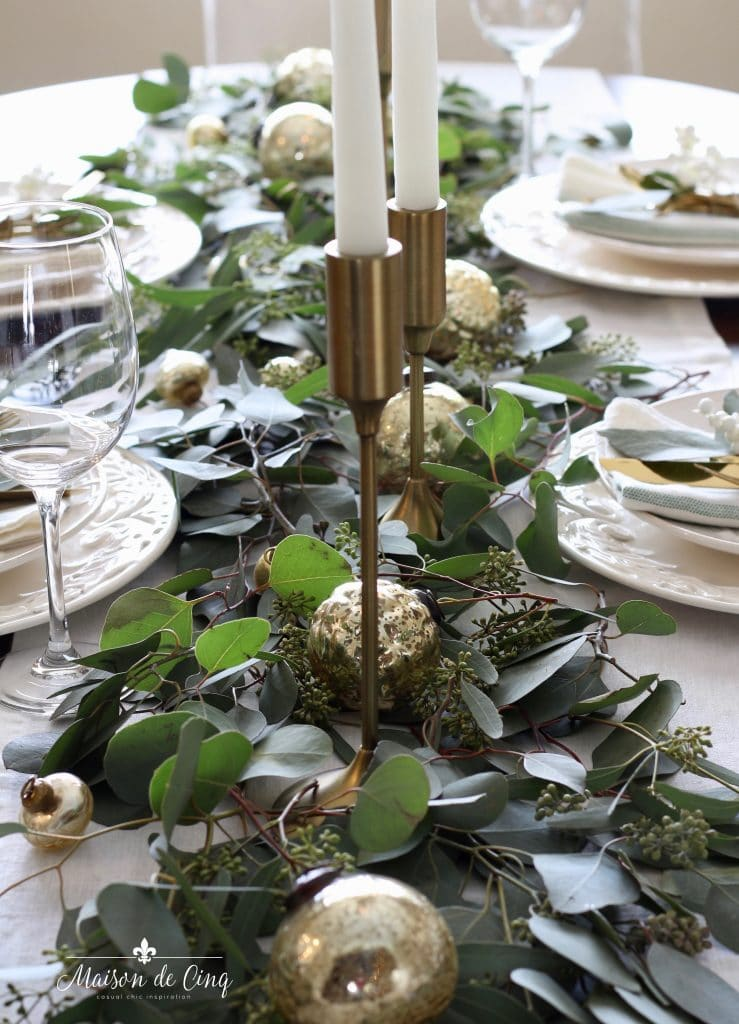 green and white christmas tablescape brass candlesticks on bed of eucalyptus with gold ornaments casual chic holiday entertaining