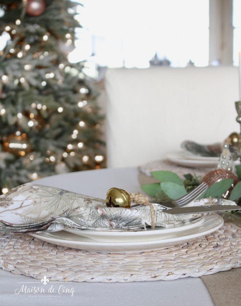 christmas table setting jute charger jingle bell napkin ring white plates and ornaments pretty holiday table
