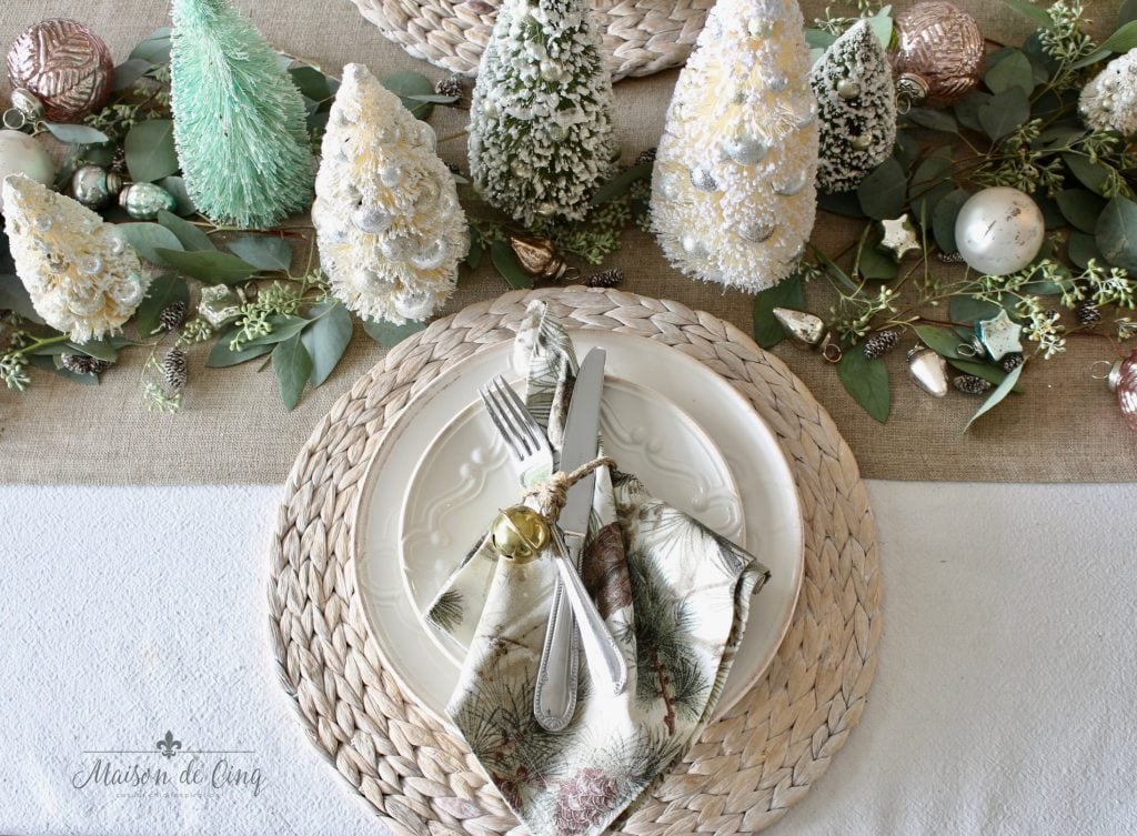 christmas table setting white plates jute chargers bottle brush trees and eucalyptus