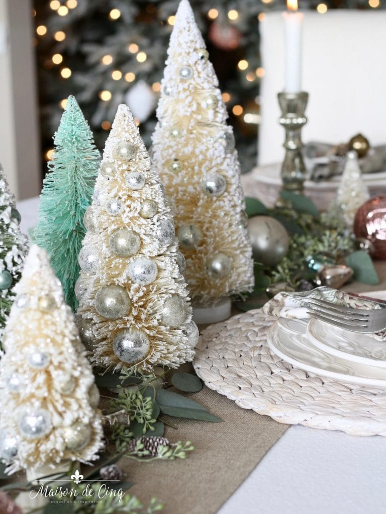 christmas table setting centerpiece of eucalyptus bottle brush trees in white and green and ornaments