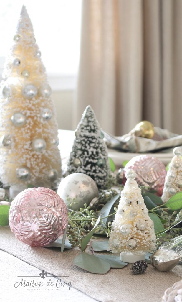 christmas table setting bottle brush trees in soft greens and white with pink and silver ornaments centerpiece