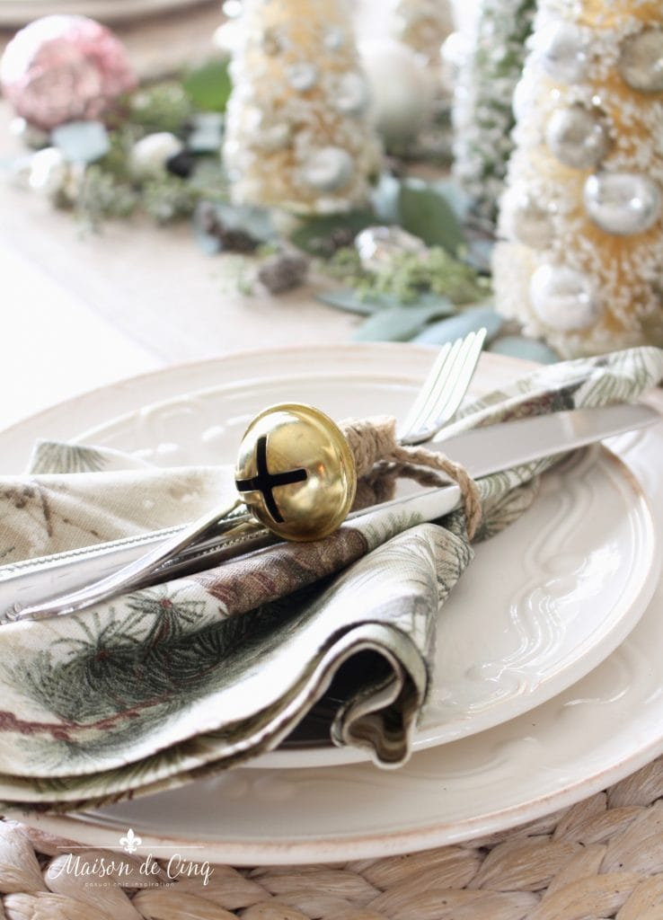 christmas table setting white plates jingle bell napkin ring and bottle brush trees