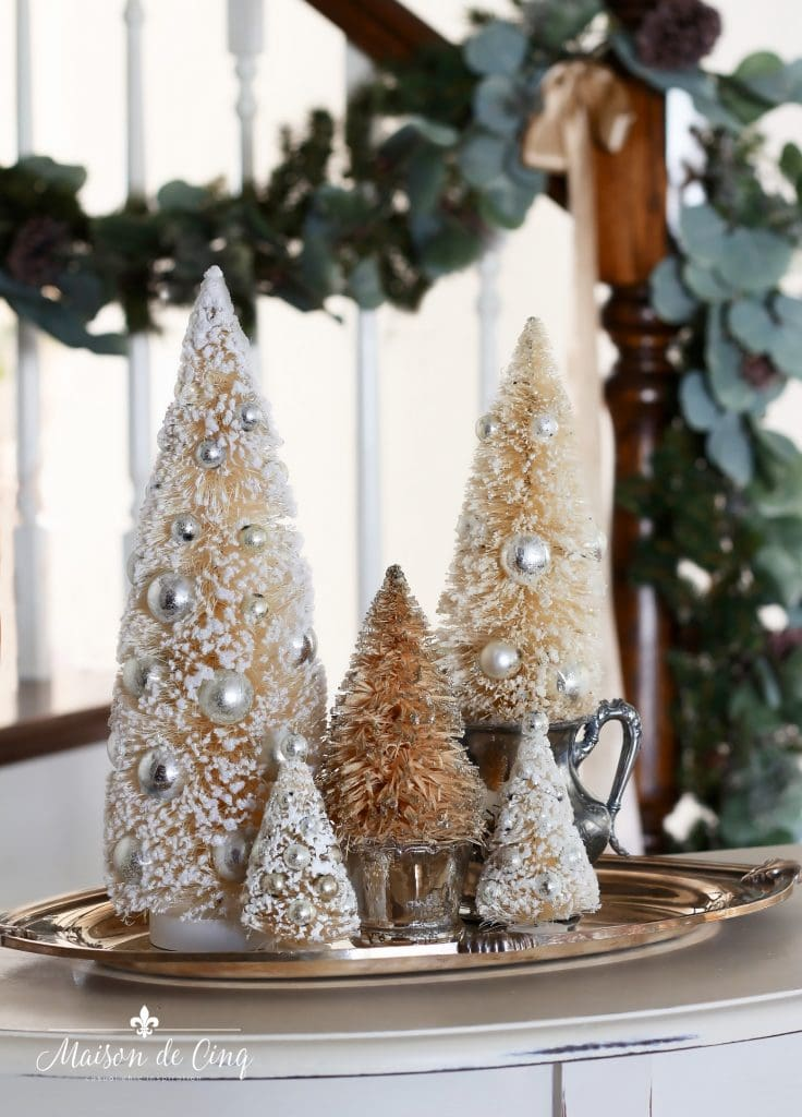 christmas entry way neutral bottle brush trees with garland on banister