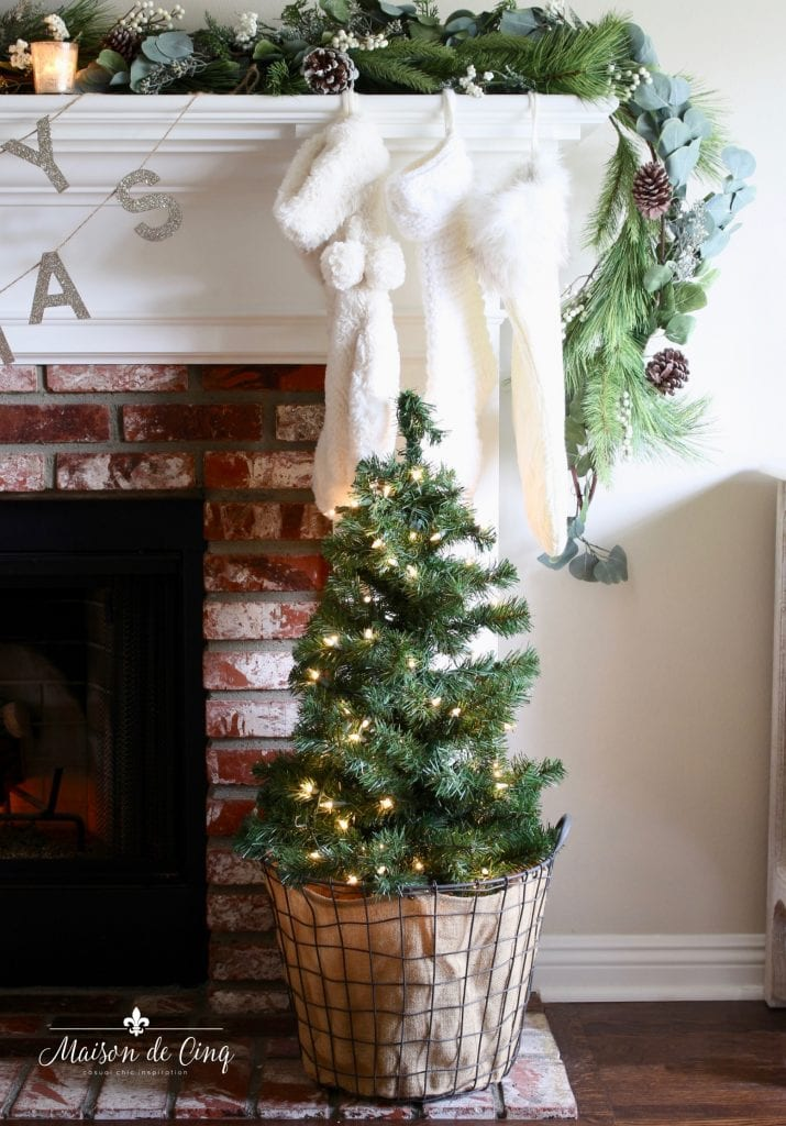 romantic Christmas living room small tree on fireplace hearth with white knit stockings french style