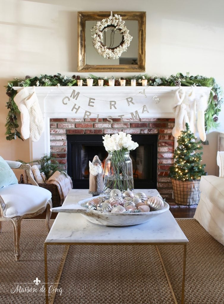 romantic christmas living room fireplace mantel with garland and white wreath and stockings