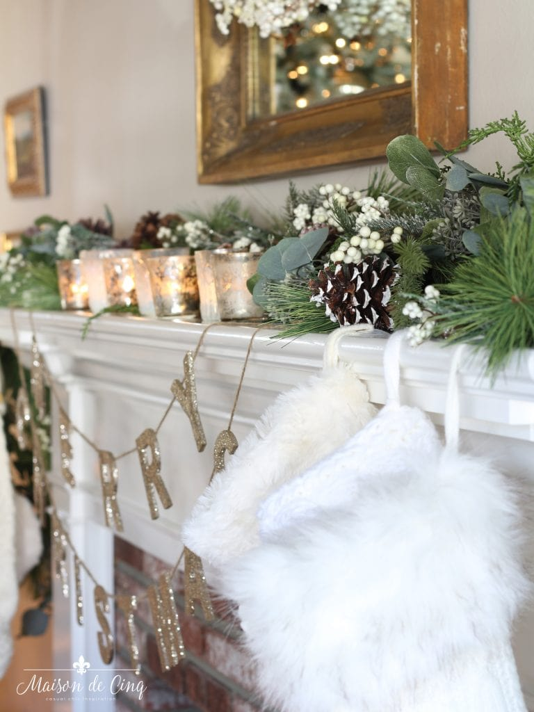 romantic christmas living room mantel with mercury glass votives and pinecones in garland