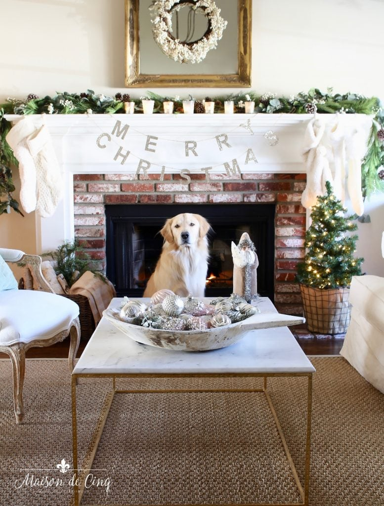 romantic christmas living room fireplace mantel with garland white stockings and wreath on mirror golden retriever