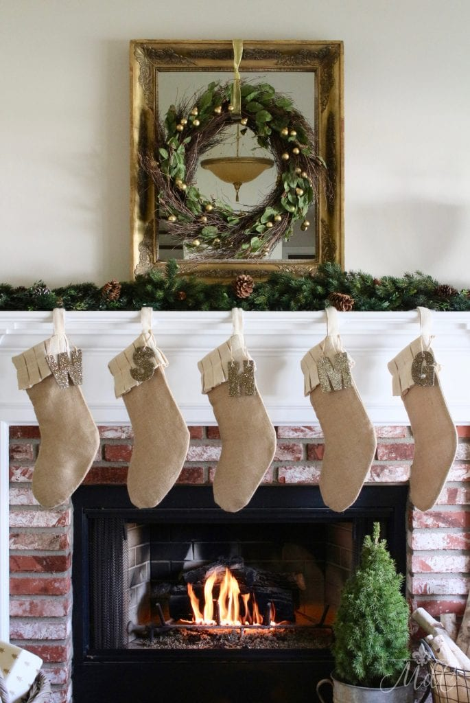 french christmas decor living room mantel with stockings, gold mirror and wreath