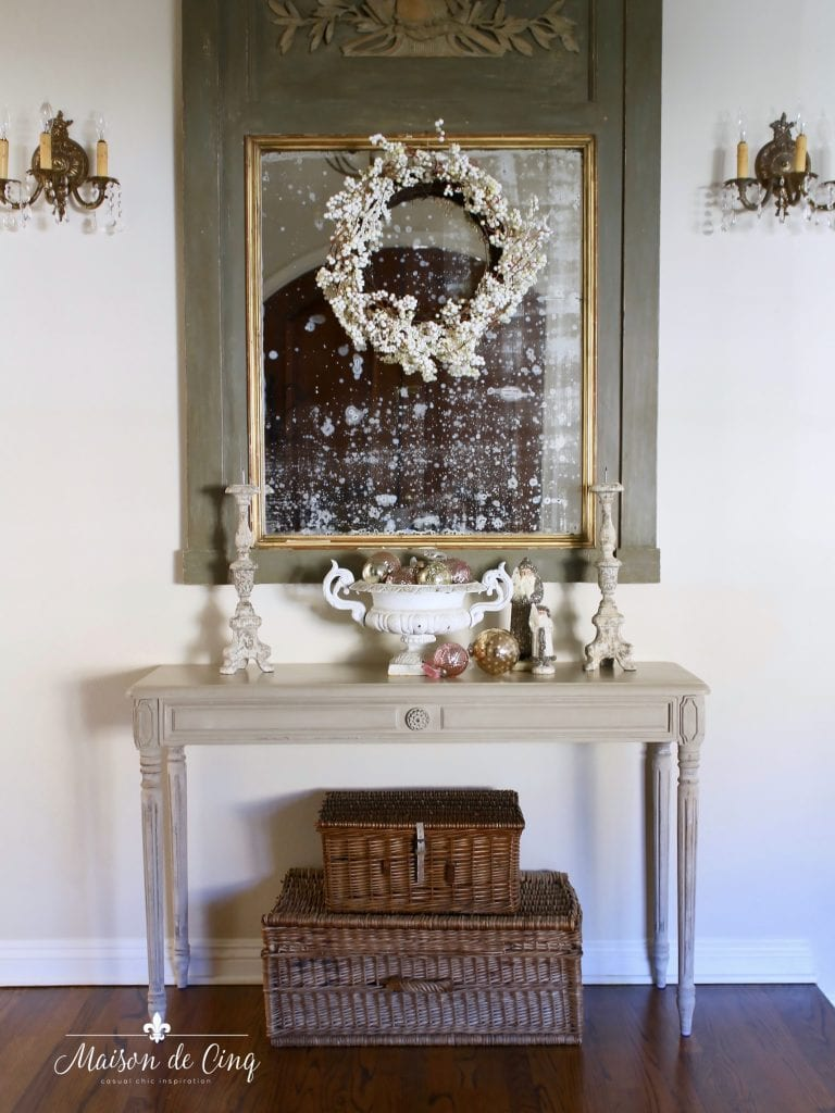 christmas entry way french mirror wreath console table with urns and baskets beneath