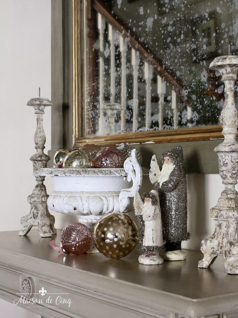 christmas entry way with french urn, ornaments, and vintage santas