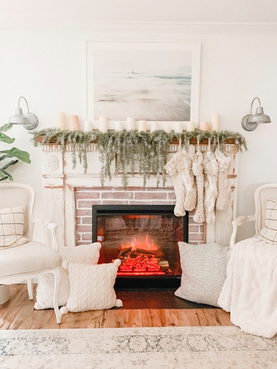 A cozy fireplace that is on with white pillows and stockings.