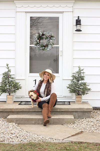 A girl on her porch with her dog.