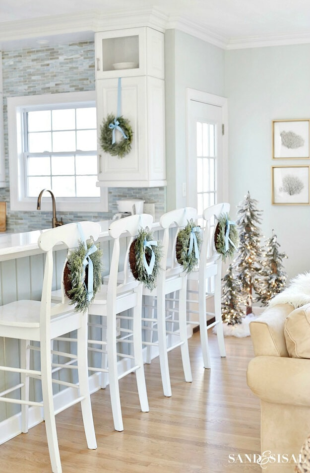 blue christmas decor ideas wreaths with blue ribbons on backs of barstools in white kitchen