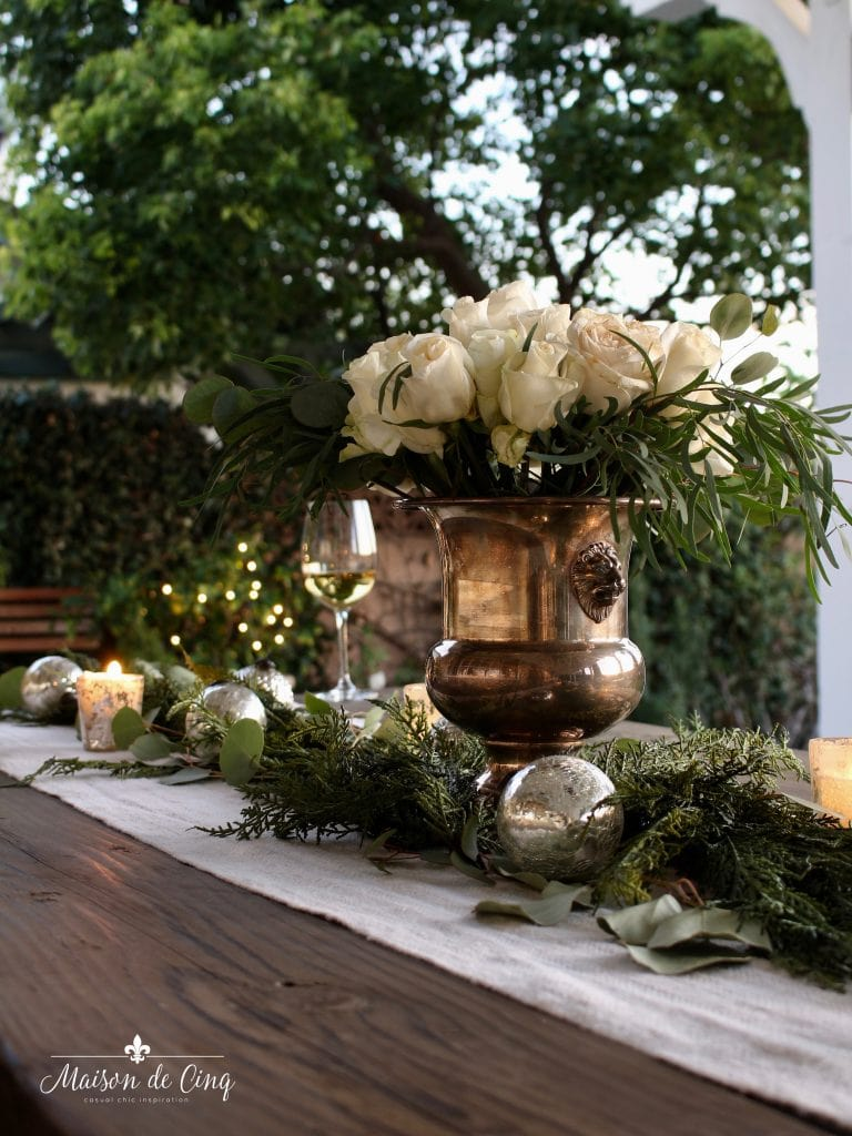 cozy Christmas patio white roses in champagne bucket on farmhouse table in the garden