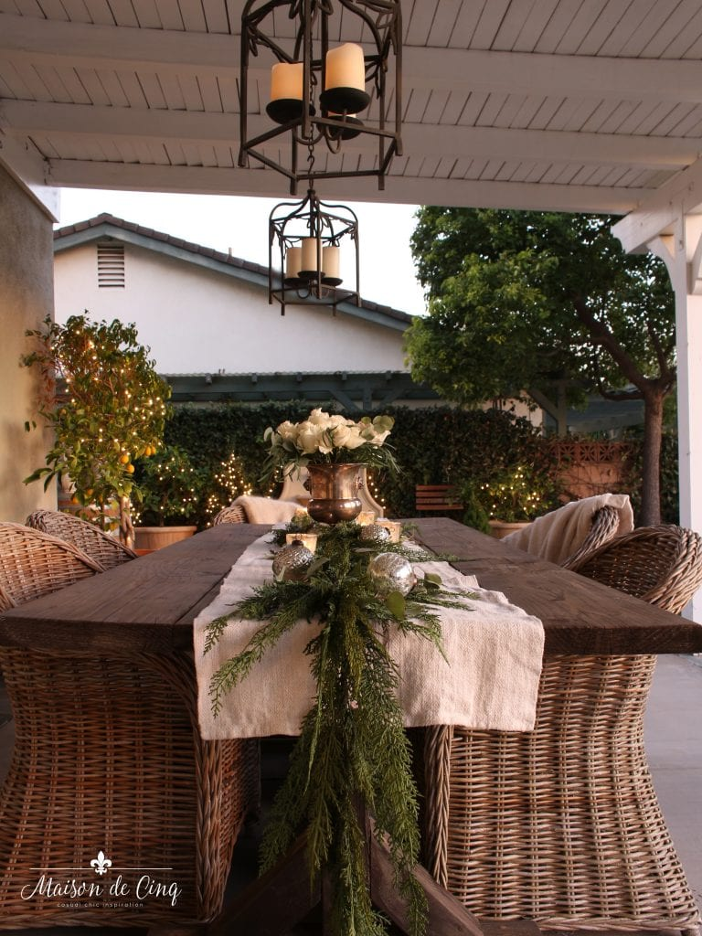 cozy Christmas patio wicker chairs farmhouse table white lights garland and white roses romantic holiday decor