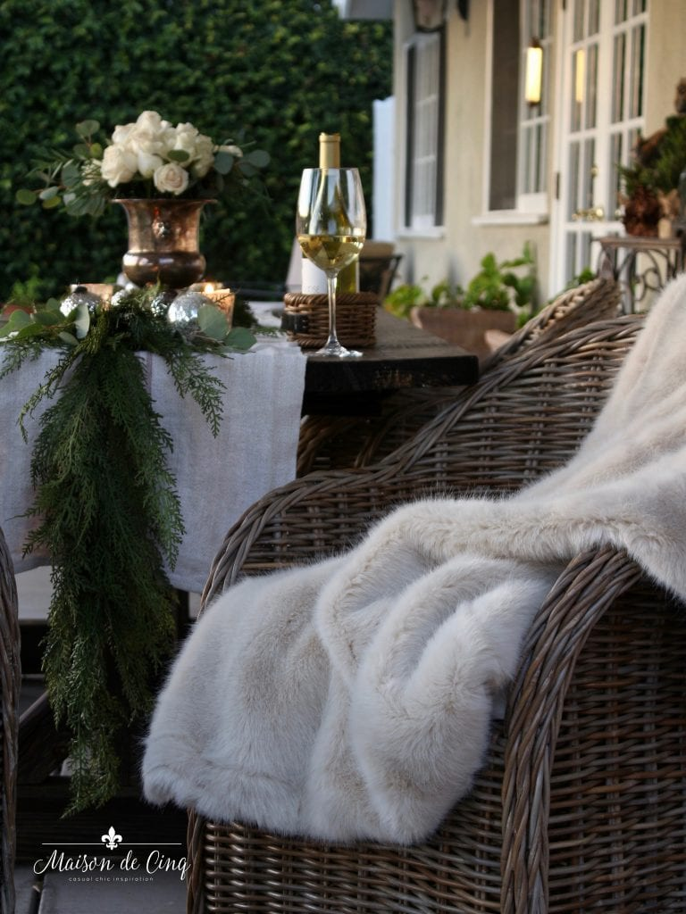 cozy Christmas patio fur blanket on wicker chair with white roses and wine