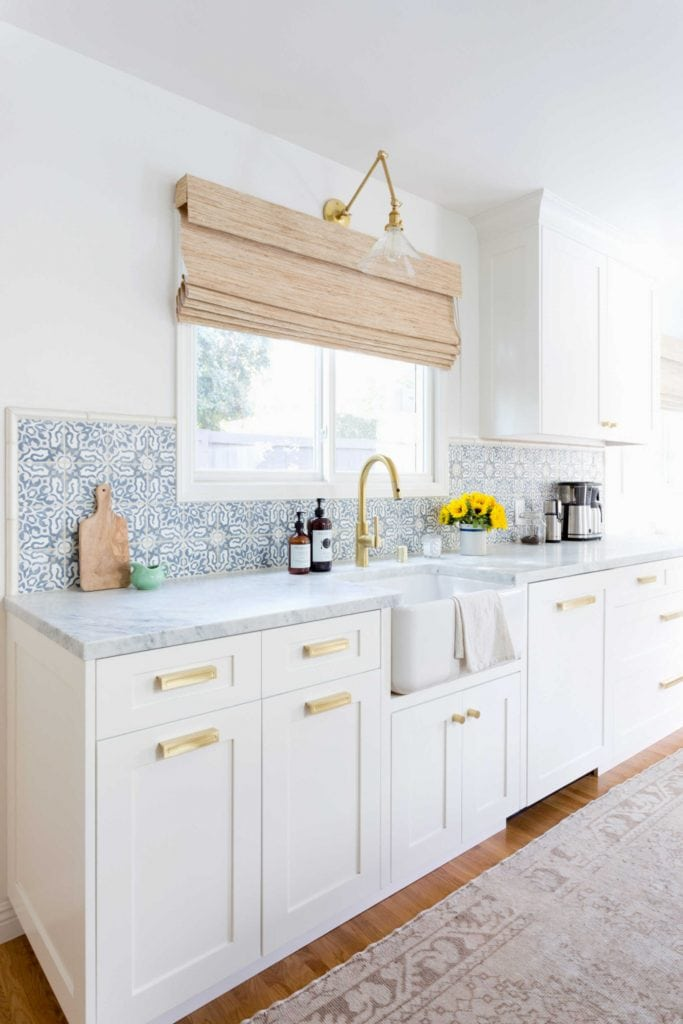blue and white cement tile in pretty white kitchen bamboo window shade