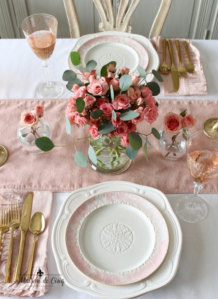 romantic Valentine's Day table for two with pink runner and napkins white plates and gold flatware