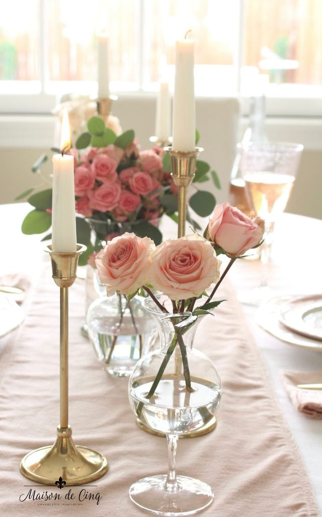 romantic Valentine's Day table brass candlesticks and pink roses on pink velvet runner