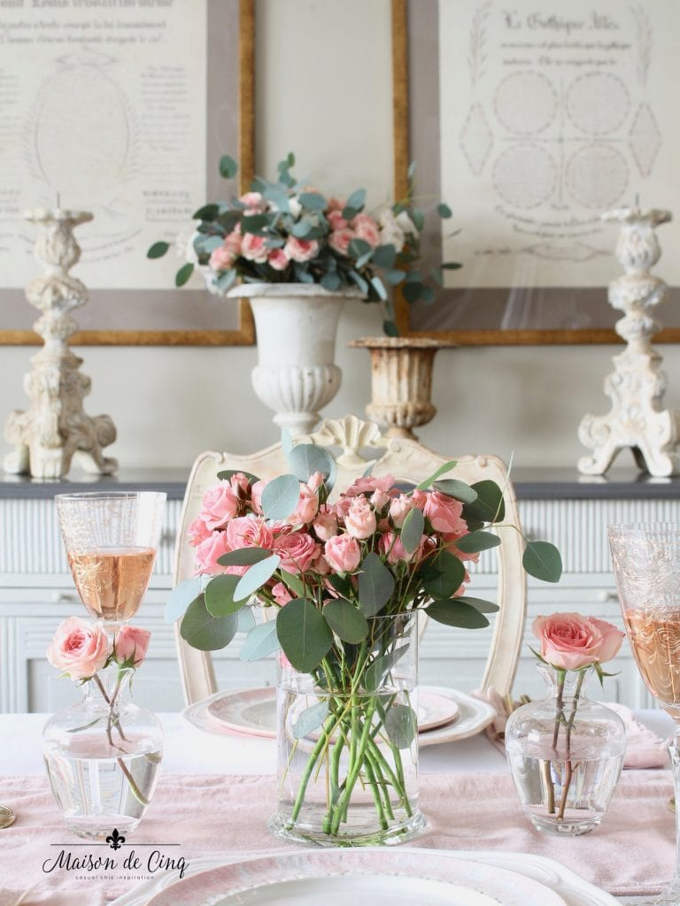 romantic Valentine's Day table with pink roses in glass vase and bud vases and gl