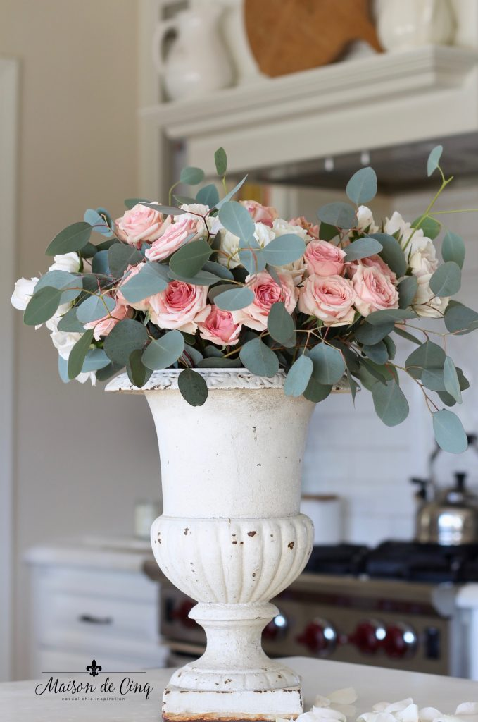 Valentine's Day decorating white French urn with pink roses in farmhouse kitchen