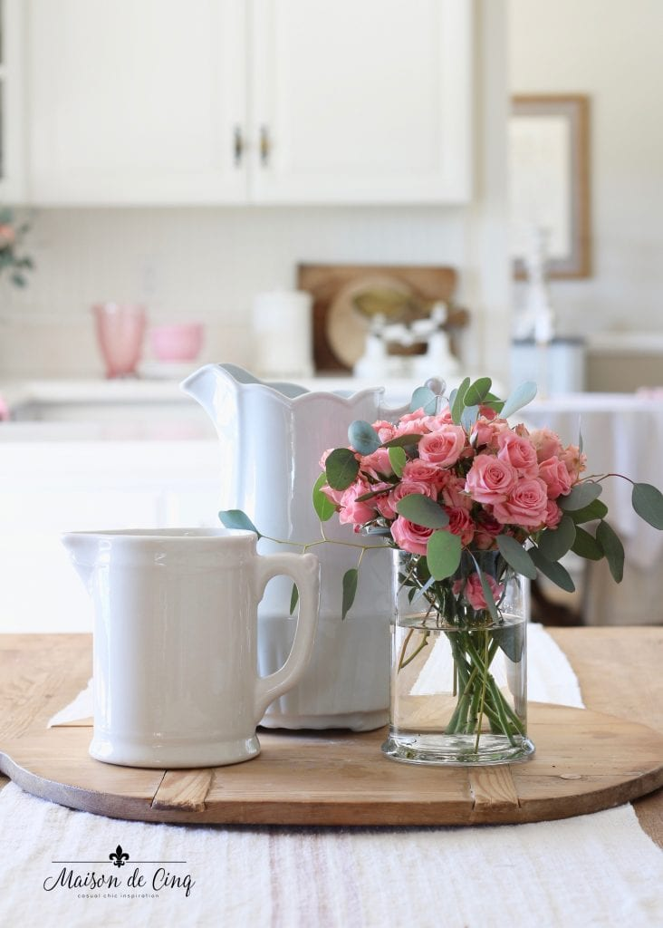 Valentine's Day decorating white ironstone pitchers with pink roses in white farmhouse kitchen