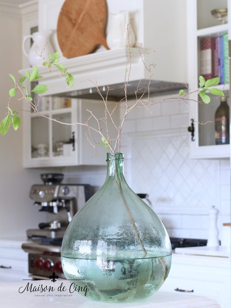 tips for winter decorating branches added to french demijohn in white french country kitchen