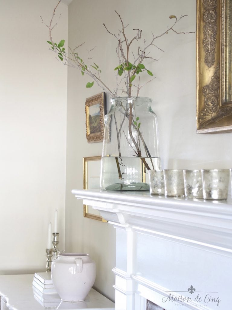 tips for winter decorating branches in a vase on mantel with silver votives