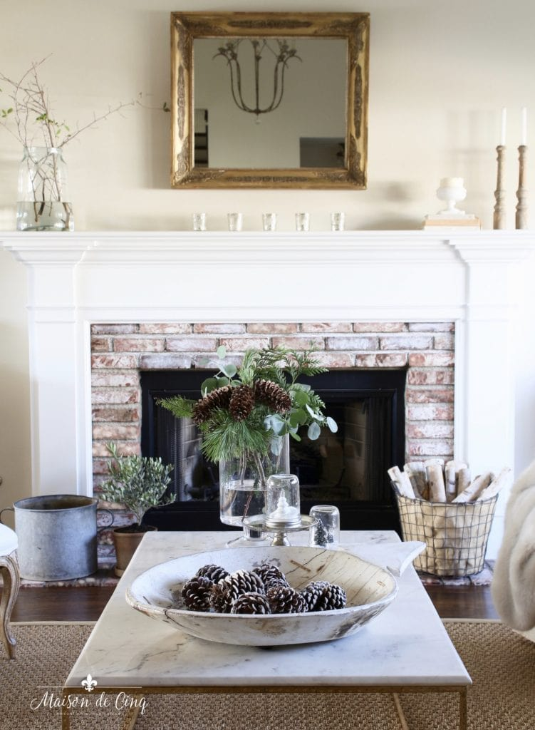 tips for winter decorating french country room fireplace mirror pine cones and greens on coffee table