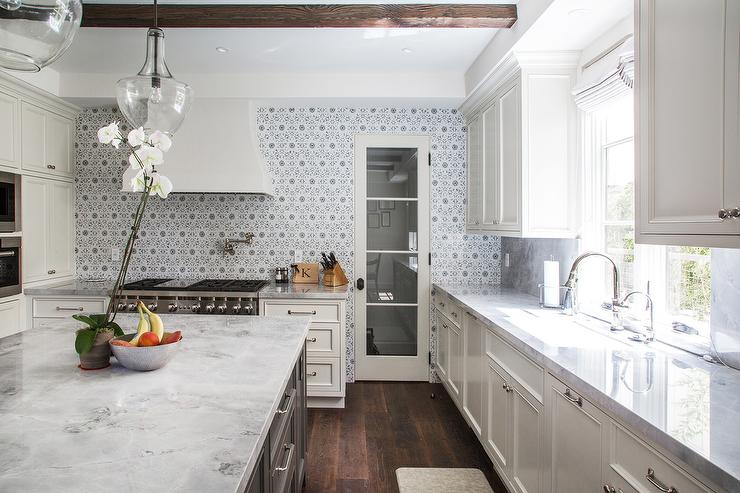 cement tile backsplash up to ceiling in white kitchen with wood beams and marble countertops