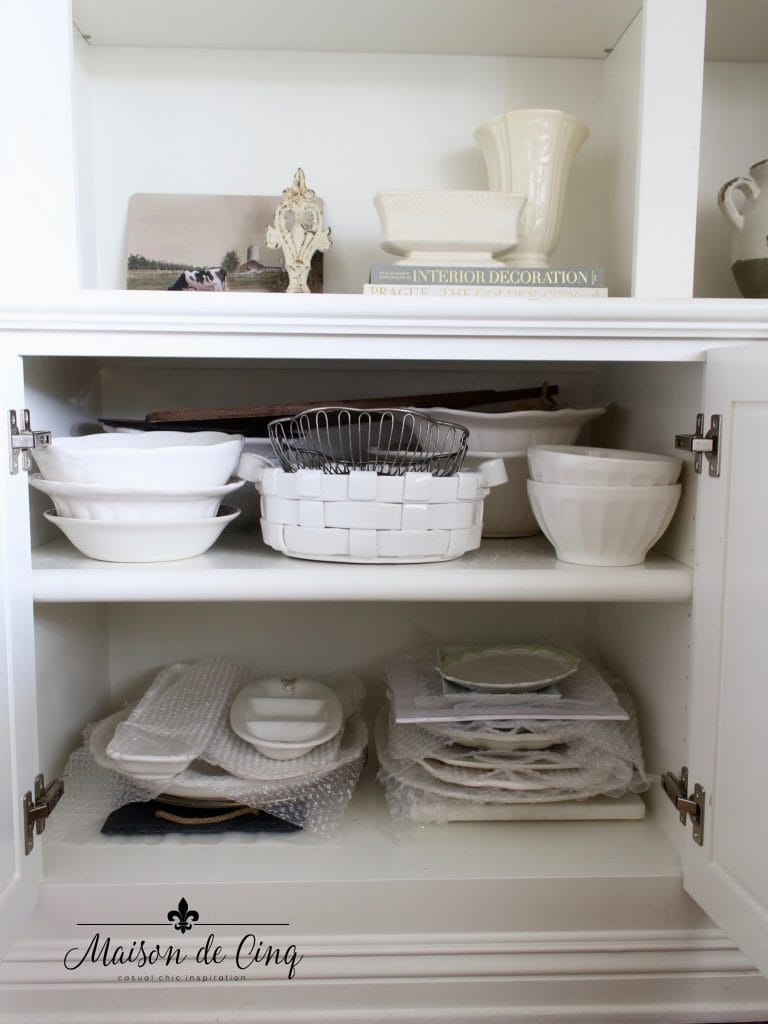 tips for organizing cabinets after shot of white dishes and platters stacked neatly
