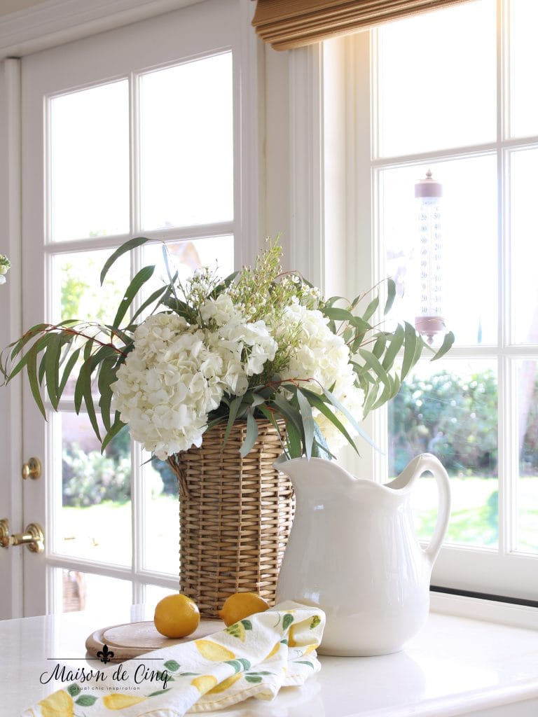 simple spring decorating white flowers in basket with white pitcher and lemons spring cheer in white kitchen