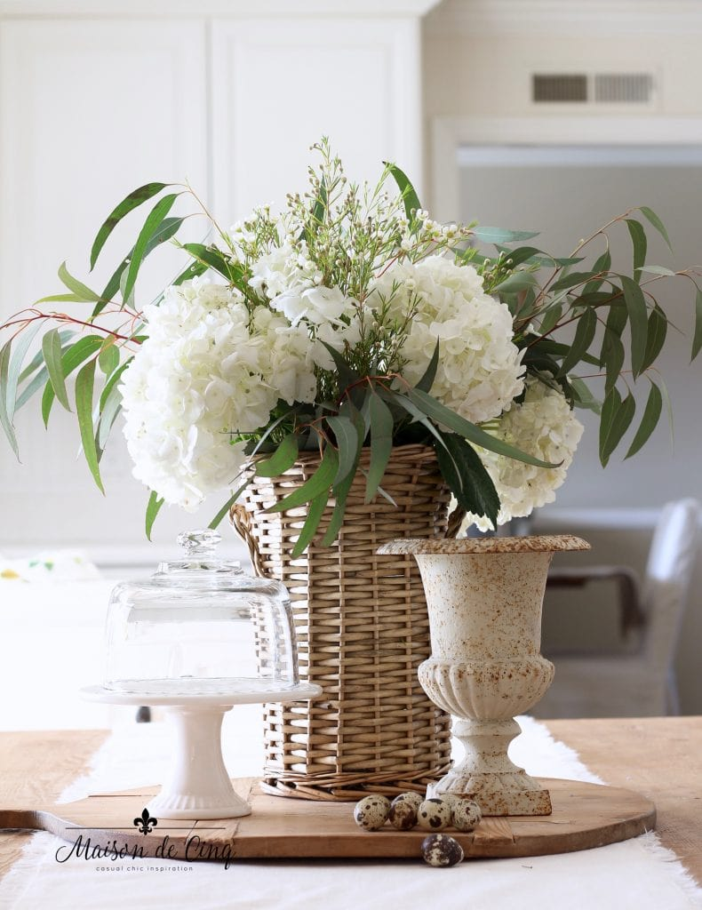 simple spring decorating wicker basket with flowers cake plate and urn french country style