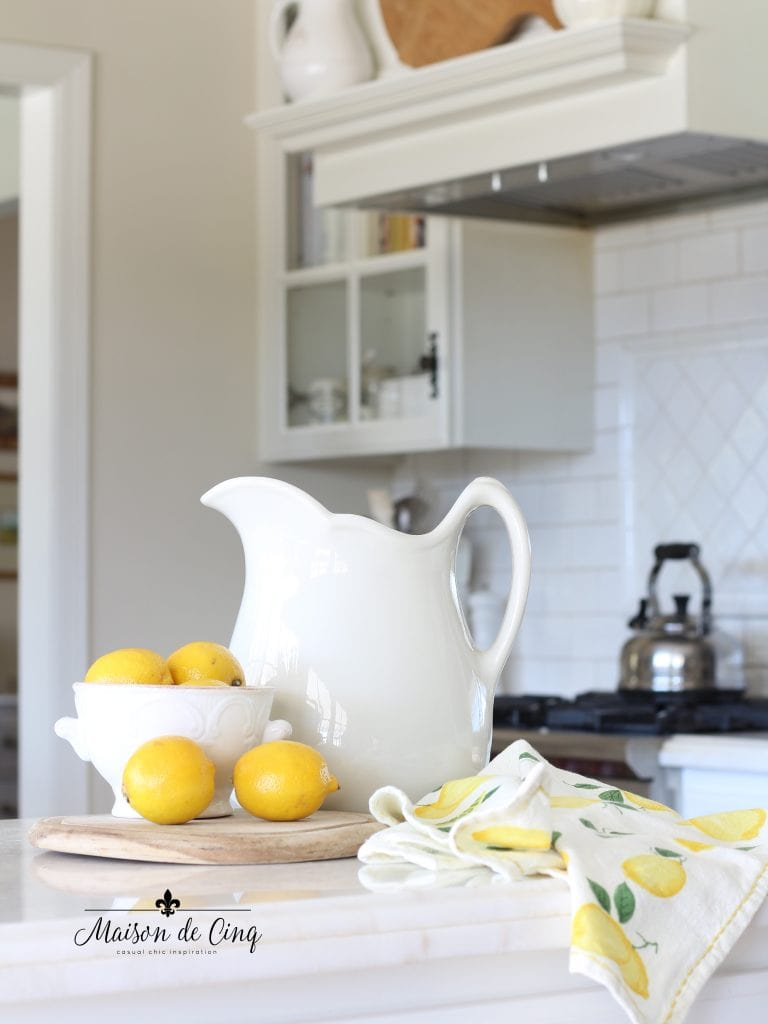 simple spring decorating white pitcher with lemons and tea towel in white farmhouse kitchen