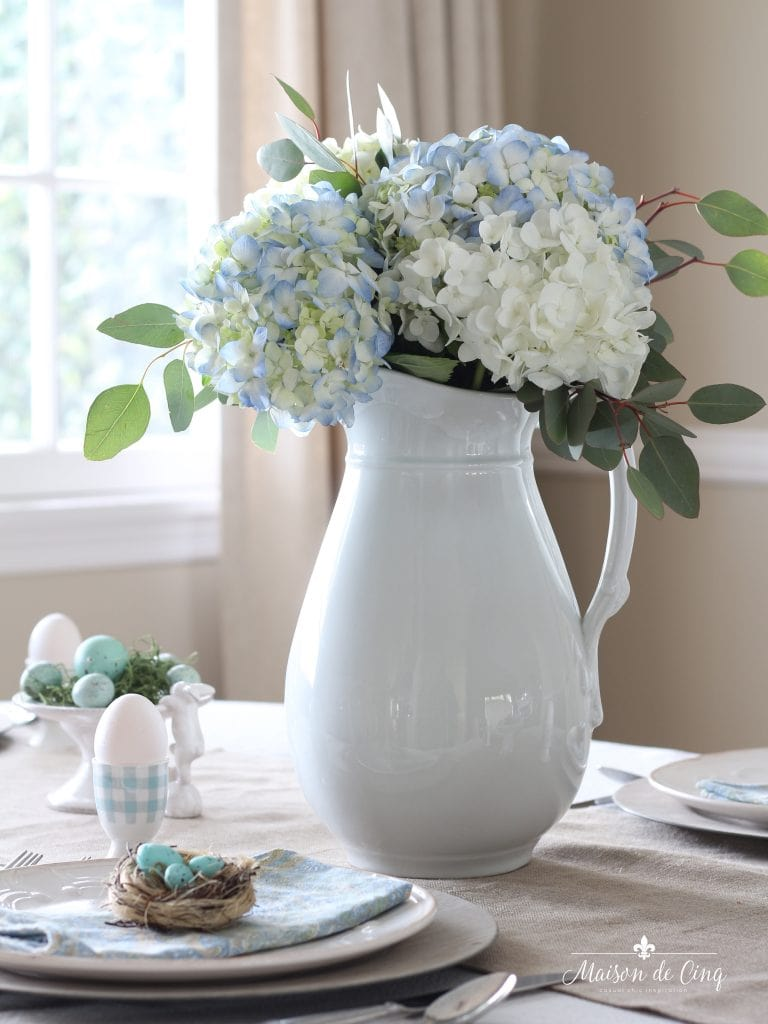 spring tablescape white pitcher with blue hydrangeas and eucalyptus blue eggs