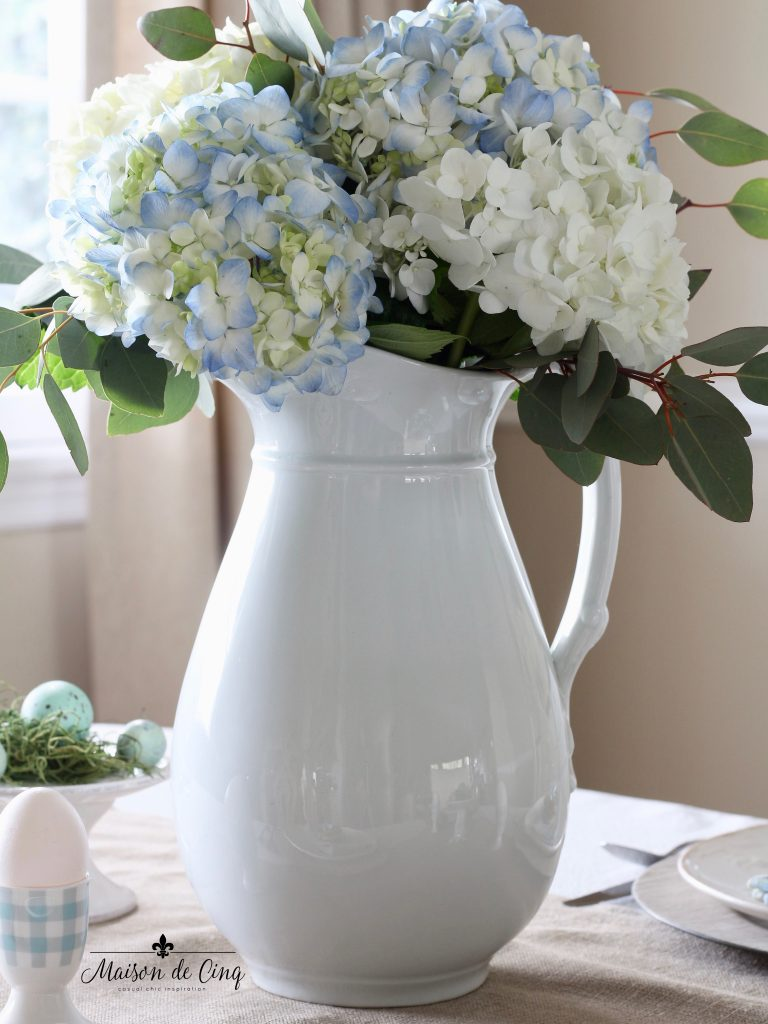 spring tablescape white pitcher with blue hydrangeas