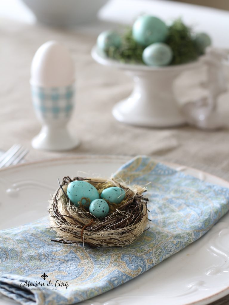 spring tablescape blue eggs in little nests on blue paisley napkin white plates