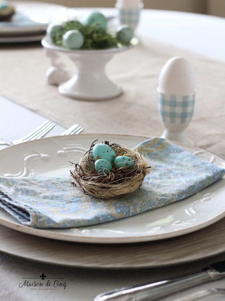 spring tablescape blue paisley napkin on white plates with nest and robins' egg blue eggs